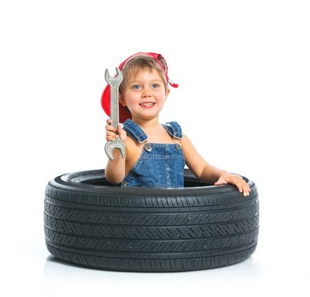 automobile workshop: Little mechanic with a tire