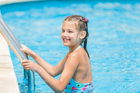 Pretty young girl at pool s edge photo