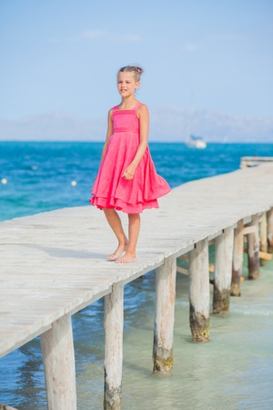 Girl walking on jetty Stock Photo