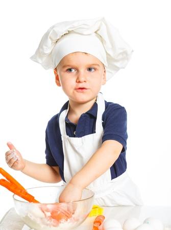 stiring: Beautiful caucasian boy making a cake