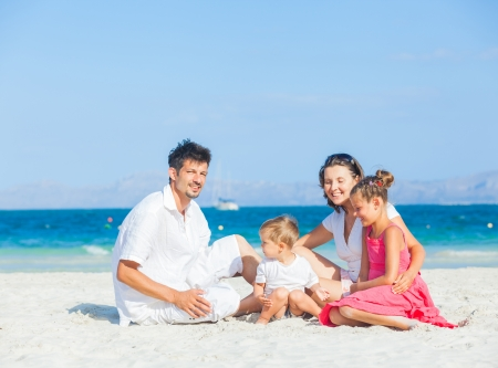 Family of four on tropical beach photo