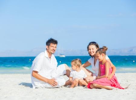 Family of four on tropical beach photo