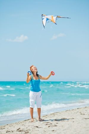 Woman on beach playing with a colorful kite Stock Photo - 13753583