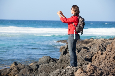 Young woman photographing a beautiful view photo