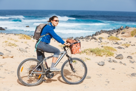 Woman riding bike on a beach photo