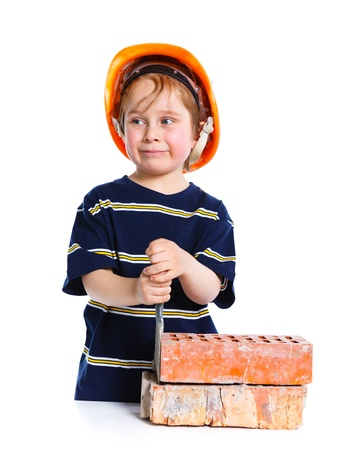 Boy in hard hat with brick photo
