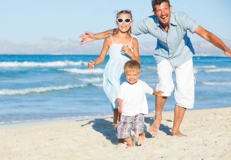 Happy family on tropical beach photo
