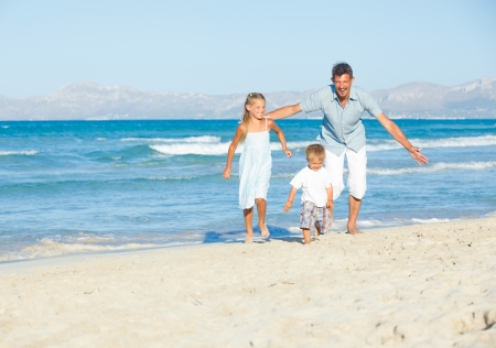 Happy family on tropical beach photo