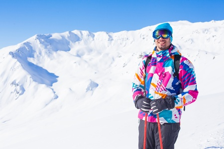 Young man with skis and a ski wear photo