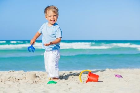 Boy with toys on beach photo