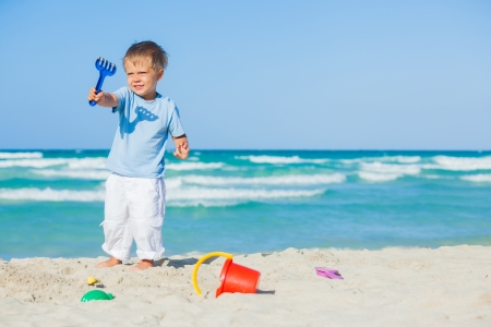 Boy with toys on beach photo
