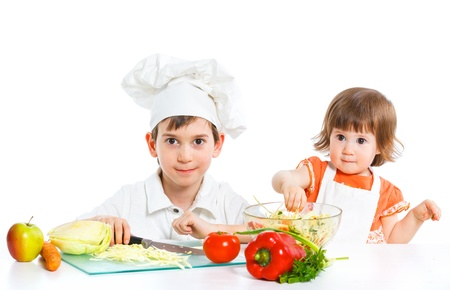 Two smiling kids mixing salad photo
