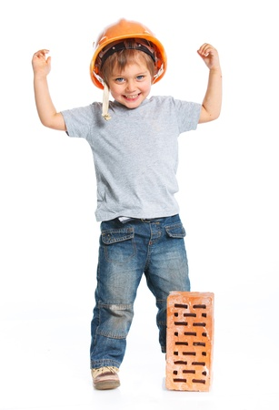 Boy in hard hat with brick photo