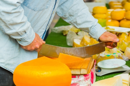 Male hands cutting dutch cheese photo