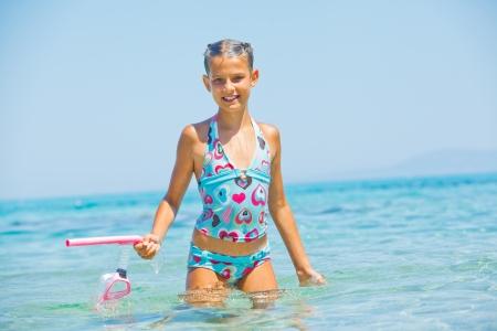 Het leuke meisje spelen in de zee Stockfoto