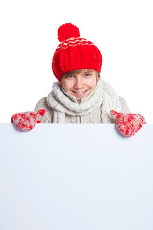 Teenager in winter style looking at a blank board photo