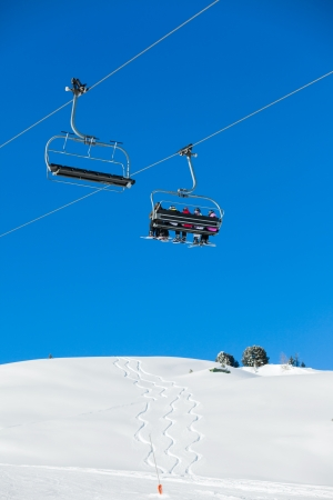 Skiers on a ski-lift photo