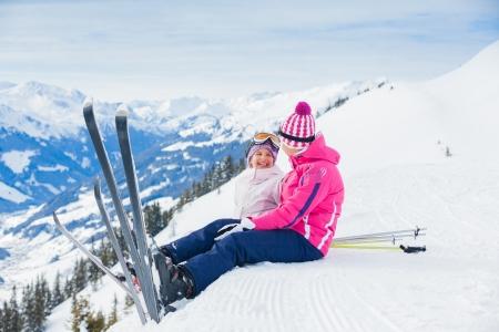 Jonge skiër zittend op de heuvel Stockfoto