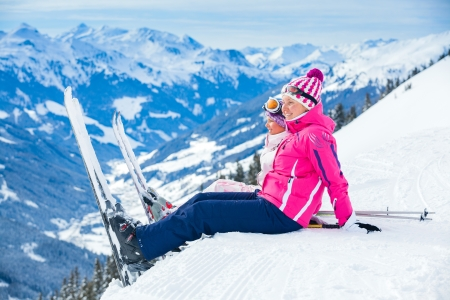 Young skier sitting on the hill photo