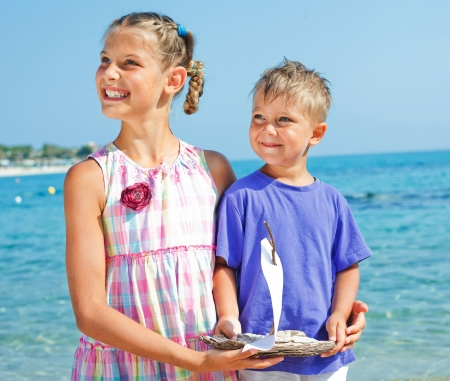 preteens beach: boy and girl with toy ship Stock Photo