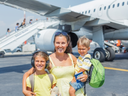 Young mother with two kids in front of airplane Stock Photo