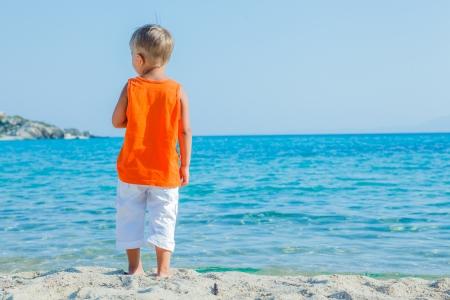 Back view portrait of cute boy at tropical beach photo