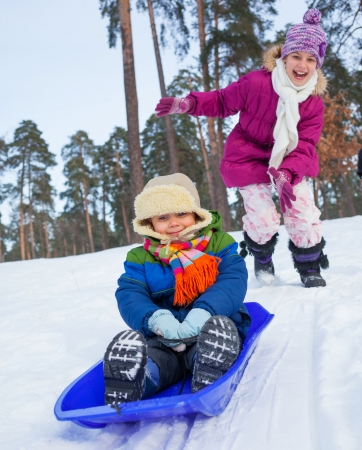 Cute sister and brother on sleds in snow forest  Focus on the boy photo