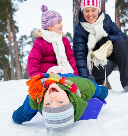 sledging people: Mother with her two kids is sledging in winter-landscape  Focus on the boy