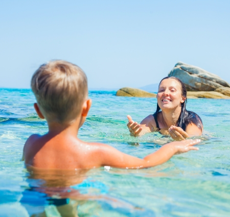 Happy young mother with her little son swimming in the transparent sea Stock Photo - 17658332
