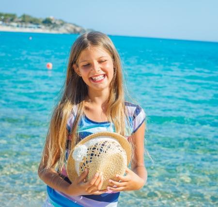 Ragazza sveglia in cappello sulla spiaggia