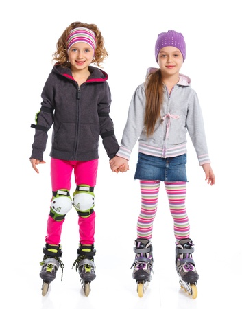 kneepad: Two cute girls holding hands wearing roller skates  Isolated on a white background Stock Photo