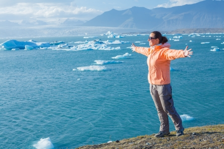 Young woman enjoying the view Jokulsarlon a lake in Iceland where icebergs collapsing from Vatnajokull glacier are floating around  Stock Photo - 17847564