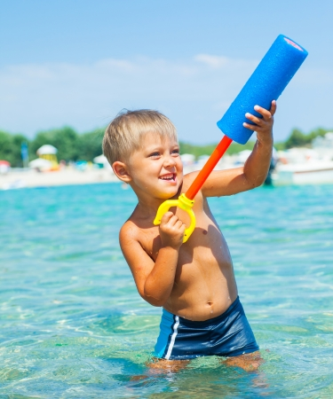 Portrait of young boy swimming and plaing water pistol in the transparent sea photo