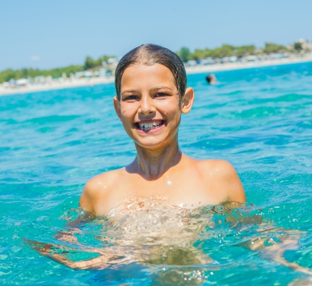 Closeup portrait of young girl swimming in the transparent sea photo