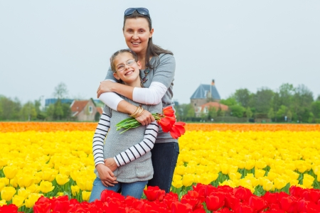 Girl and her mother with bouquet between of the yellow-red tulips field photo