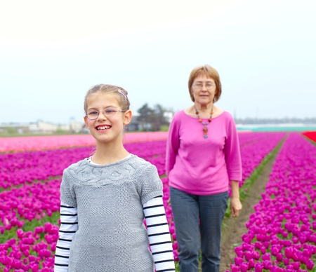 Girl with her grandmother walks between of the purple tulips field Stock Photo - 17860715