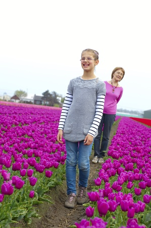 Girl with her grandmother walks between of the purple tulips field Stock Photo - 17858724