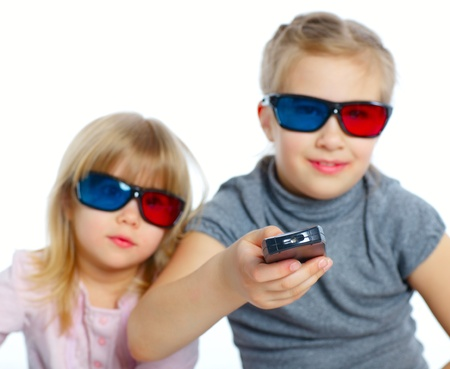 3 d glasses: Studio shot of two girls in 3d glasses with control panel watching TV  Focus on the control panel  Isolated white background Stock Photo
