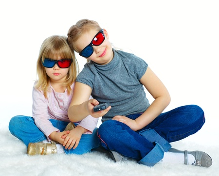 3 d glasses: Studio shot of two girls in 3d glasses with control panel watching TV  Isolated white background