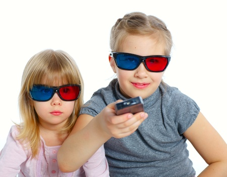 Studio shot of two girls in 3d glasses with control panel watching TV  Isolated white background photo