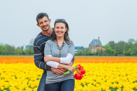 Young happy couple in the yellow tulip fields from the Netherlands Stock Photo - 17887204