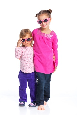 Two happy adorable smiling sisters in sunglasses  Isolated white background photo