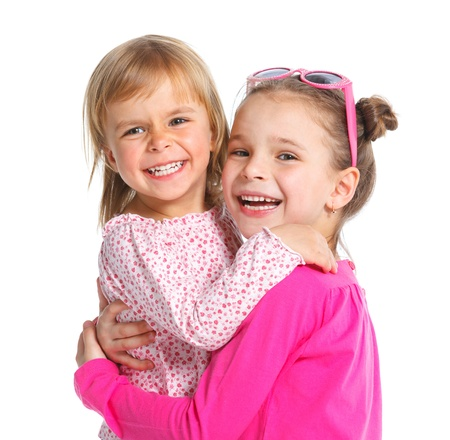 Two happy adorable smiling sisters  Isolated white background photo