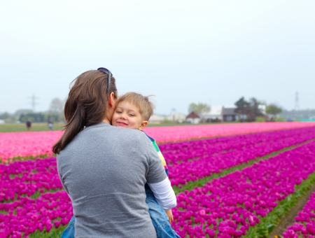 Little boy and his mother with bouquet between of the yellow-red tulips field Stock Photo - 17887051