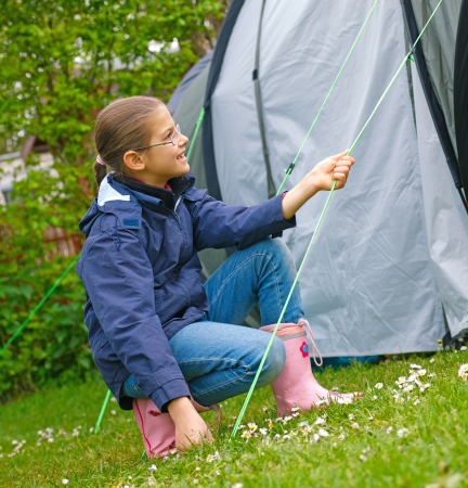 camping pitch: Young girl out camping learning how to pitch tent