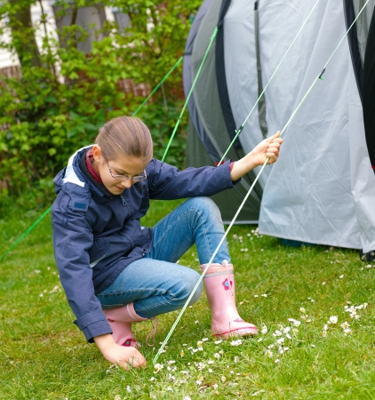 Young girl out camping learning how to pitch tent photo