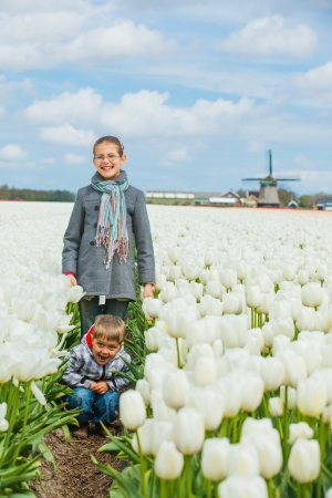 Boy with his sister runs between of the purple tulips field  Vertical view photo