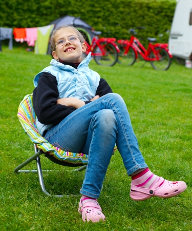 recliner: Spring vacation in camping - Cute girl resting in the colorful recliner