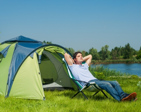 chaise lounge: Holiday camping - Young man resting in a chaise lounge near A Tent In The Countryside