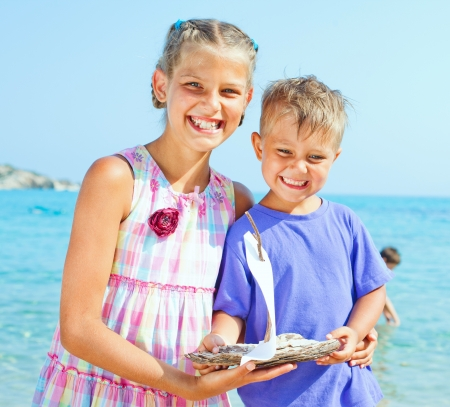 ashore: Cute boy and girl with toy ship in hands ashore
